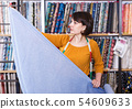 Saleswoman measuring cloth for cutting 54609633