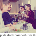Group of sociable friends enjoying evening meal at restaurant 54609634
