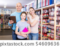 parents with daughter buying school supplies 54609636