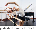 Choreographer woman and young man do exercises at ballet bar in hall with mirror 54609640