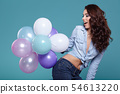 Happy young woman standing over blue wall and 54613220
