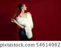 Portrait of glam girl in white fur on red background. Fashion photo 54614062