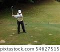 Golfer hitting tee shot in middle hole 54627515