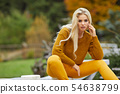 Autumn woman relaxing on a wooden terrace in the 54638799