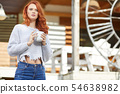 Woman drinking coffee at terrace on a sunny 54638982