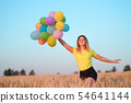 Young girl with colorful balloons in sunset meadow 54641144