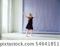 Girl in black dress dances alone to music 54641851