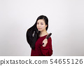 Young woman brushing her hair with a brush on the left hand in front of a white background 54655126