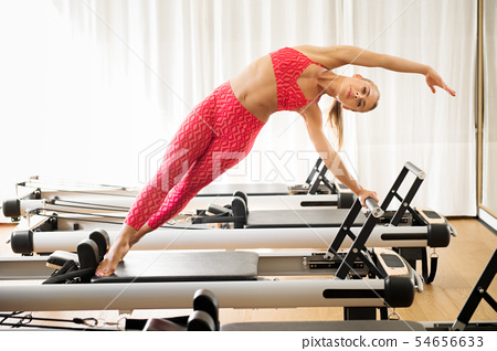 Woman exercising mermaid stretch on reformer bed 54656633