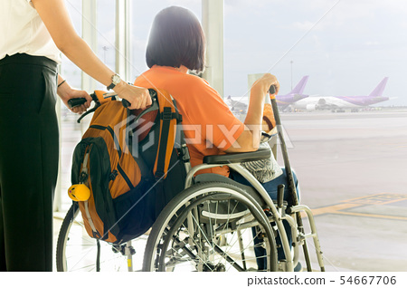 Woman with mother in wheelchair waiting for boarding at International airport. 54667706