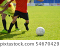 Young football players play football at  stadium 54670429