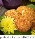 Mooncakes, teapot, yellow chrysanthemum flowers. 54673512