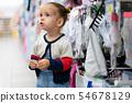A little Caucasian girl is standing near a shop 54678129