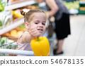 Little Caucasian girl chooses fresh vegetables in 54678135