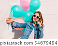 Happy birthday girl with balloons making selfie 54679494
