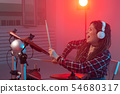 Hobby, music and people concept - Excited woman playing the electronic drum set 54680317