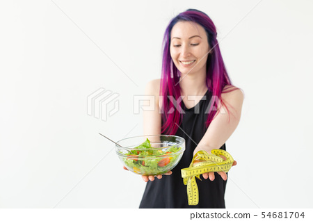 Young asian girl hipster colored hair holding in hands a measuring tape and vegetable salad posing 54681704