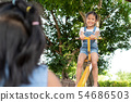 Two cute asian child girls playing seesaw together 54686503