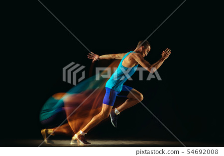 Professional male runner training isolated on black studio background in mixed light 54692008