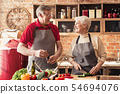 Cheerful senior man and woman cooking healthy salad at kitchen 54694076