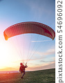 Man holds paraglider slings and prepares to start 54696092
