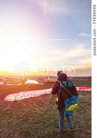 Landed man folds parachute lying on green grass 54696099
