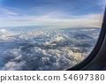 Aerial view sky and clouds through the plane illuminator after aircraft take off. 54697380