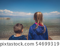 Little children standing on the lake shore 54699319