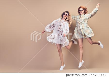Fashion. Two happy woman jumping dance Having Fun 54708439