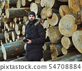 Portrait of a man in the background of a huge pile of trees 54708884