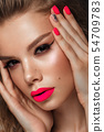 Beautiful young woman with bright makeup and neon pink nails. Beauty face. Photo taken in the studio 54709783