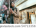 woman holding smart phone in front of restaurant 54713356