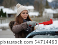 Young female sweeps snow off her car 54714493