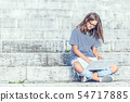 Young schoolgirl sitting on stairs with laptop and 54717885