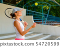 young sportive woman throwing a tennis ball 54720599
