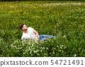 Man lying in a flower meadow 54721491