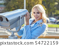 Cheerful young tourist using telescope  tower 54722159