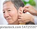 Doctor help patient wear audiphone 54725597