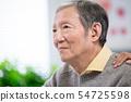 Doctor help patient wear audiphone 54725598