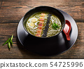 Green spinach soup in black bowl with tuna, quail an egg, black sesame seeds. Wooden table on 54725996