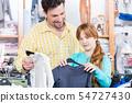 Daughter choosing t-shirt in the retail shop 54727430