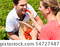 Woman feeding man strawberries she picked herself 54727487