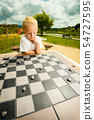 Child playing draughts or checkers board game 54727595