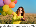 Young girl with big bunch of colorful balloons 54729297