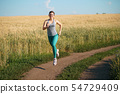 Woman jogger working out in the morning sunny day 54729409