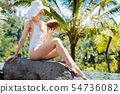 Woman on poolside with coconut relaxing in the holidays 54736082