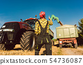 Farmer woman watching the wheat being loaded during harvest 54736087