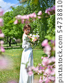 Bride with a bouquet of flowers in the summer park 54738810