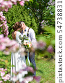 Bride and groom in a bouquet kiss in a green park 54738831