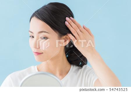 檢查頭髮的女人(藍色背景) 54743525